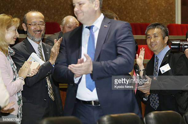 Japanese astronaut Koichi Wakata and others applaud at the RKA Mission Control Center near Moscow on July 9 after a Russian Soyuz spacecraft carrying...