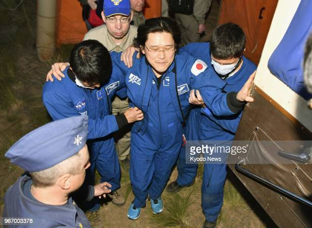 Japanese astronaut Norishige Kanai walks with support of staff in Kazakhstan on June 3 after returning to Earth following a longterm mission at the...