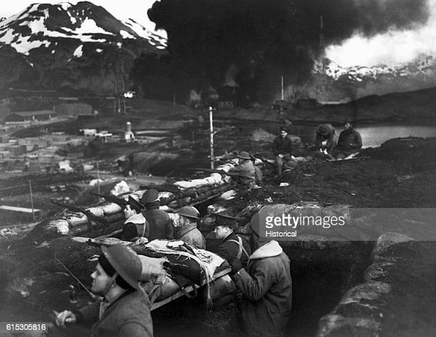Japanese attack Dutch Harbor June 3 1942 Group of Marines on the alert between attacks Smoke from burning fuel tanks in background had been set afire...
