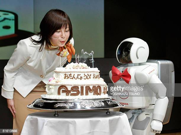 Japanese auto giant Honda Motor's humanoid rorbot Asimo helped by a Honda employee blows out candles on a large birthday cake to celebrate his 4th...