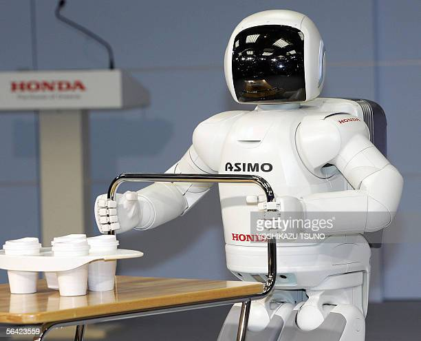 Japanese auto giant Honda Motor's new humanoid robot Asimo, which enables to run at a speed of 6kph and to run in a circular pattern, pushes a cart...