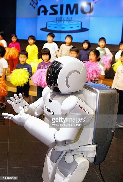 Japanese auto giant Honda's humanoid robot Asimo applauds at a ceremony to mark his second birthday as kindergarten children look on at Honda's...