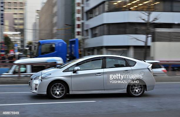Japanese auto giant Toyota Motor's hybrid vehicle Prius is driven on a street in Tokyo on February 12 2014 Toyota announced a global recall of 19...