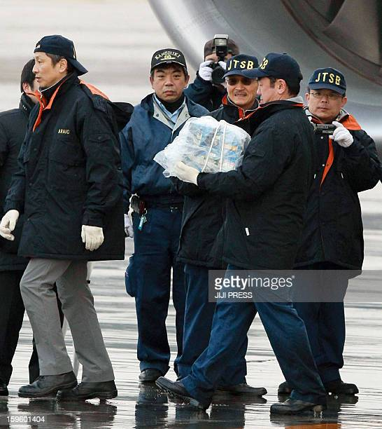 A Japanese aviation expert carries a battery which leaked electrolyte out of a All Nippon Airways Boeing 787 Dreamlier plane at Takamatsu airport in...