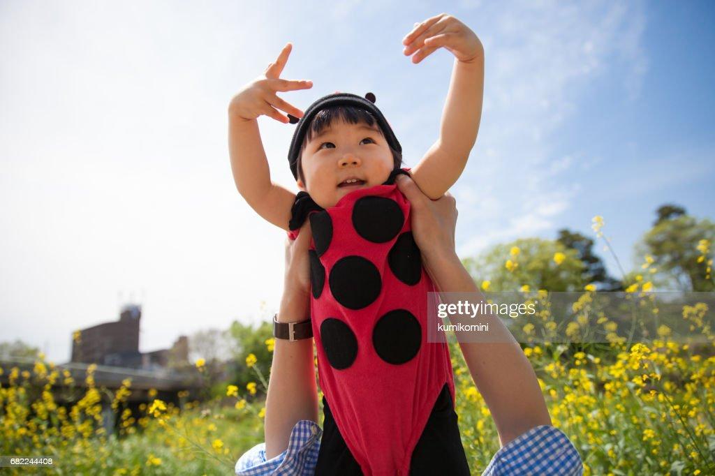 4bf1392e9e Japanese baby girl flying over flower garden in ladybird clothing   Stock  Photo