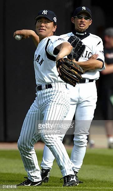 Japanese baseball AllStars Hideki Matsui of the New York Yankees throws the ball back as countryman Ichiro Suzuki of the Seattle Mariners looks on in...