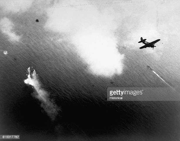 Japanese battleship Yamato burning and under attack by US carrier planes on the day it was sunk 50 miles SW of Kyushu Japan An SB2c Curtiss Helldiver...