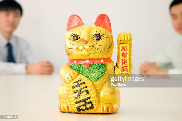 a japanese beckoning cat sitting on a table - maneki neko stock photos and pictures