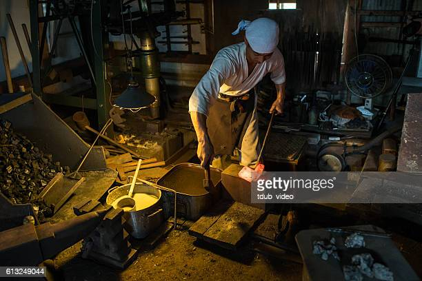 Japanese blacksmith hammers hot steel in his forge