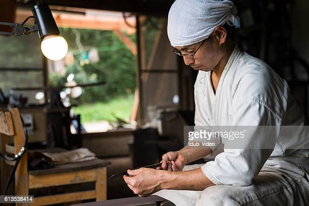 japanese blacksmith inspecting the quality of a knife blade - 美術工芸 ストックフォトと画像