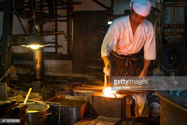 Japanese blacksmith pounds red hot steel while forging a sword