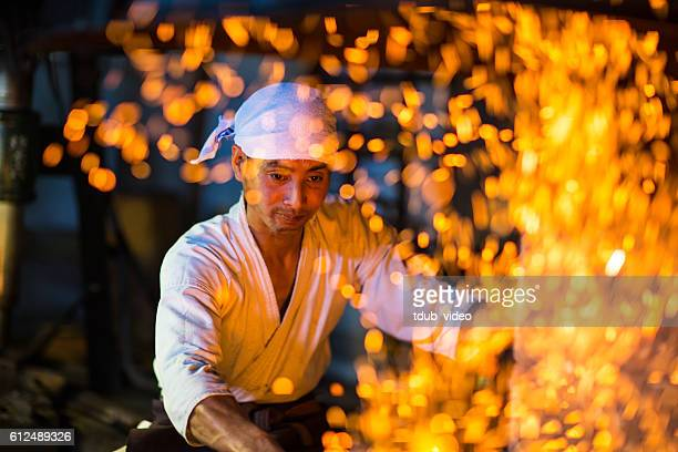 japanese blacksmith stokes a fire preparing to forge a sword - tdub_video stock pictures, royalty-free photos & images