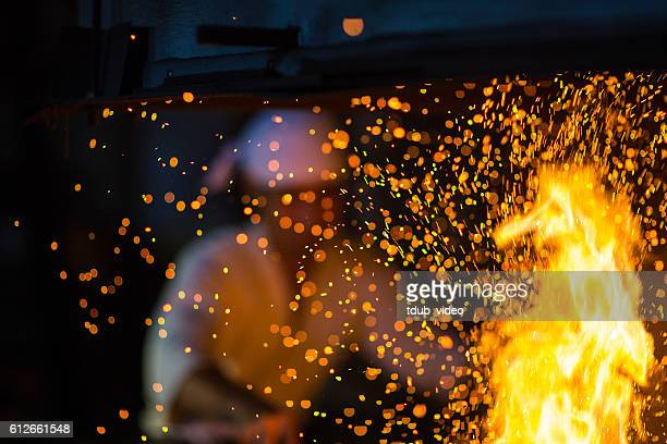 Japanese blacksmith stokes a fire preparing to forge a sword