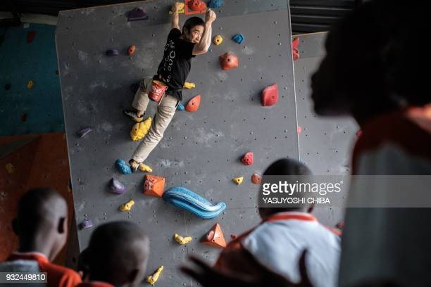 TOPSHOT Japanese blind free climber Koichiro Kobayashi reacts as he reaches to the top of the artificial climbing wall during a weeklong free...