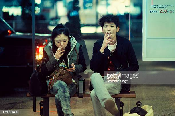 Japanese boy and girl hanging out at a bus stop, smoking while passing the time. The girl checks her mobile phone as the boy waits.