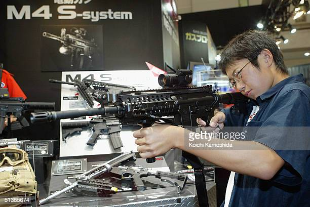 Japanese boy holds an Automatic Electric Gun at the Tokyo Marui Co Ltd booth during the All Japan Plamodel Radicon Show 2004 at Tokyo Big Sight on...