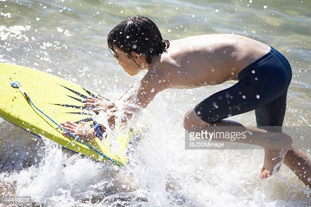 Japanese boy playing with body board in water's edge