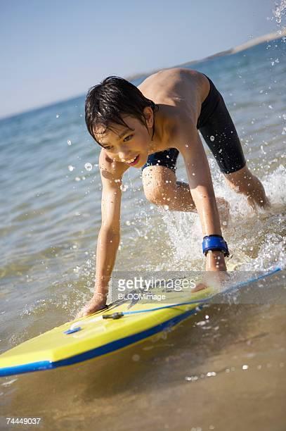 japanese boy playing with body board in water's edge - 12 13 jahre fotos boys stock-fotos und bilder
