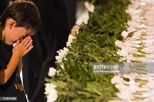 Japanese boy prays for victims of March 11 earthquake and tsunami after offering a flower during a memorial service on September 11 2011 in...