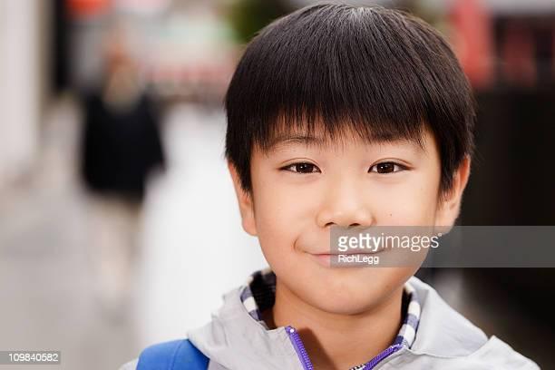 日本の少年、街の通りの上に立つ