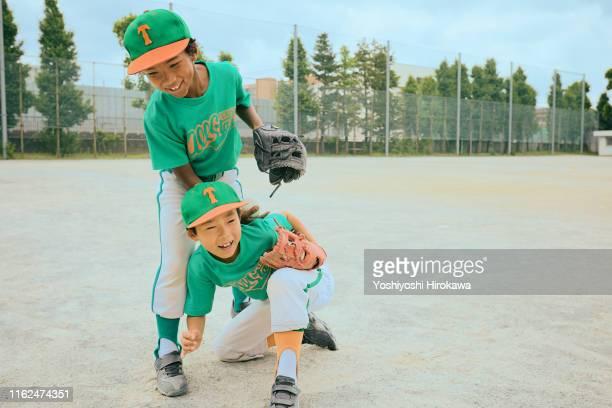 japanese boy(6-8) baseball player encouraging friends - 野球帽 ストックフォトと画像