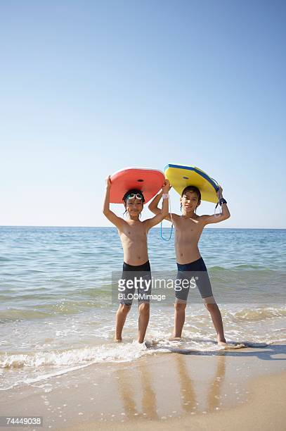 Japanese boys holding body board in water's edge