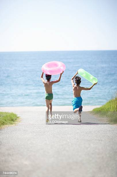 Japanese boys running with holding swimming ring