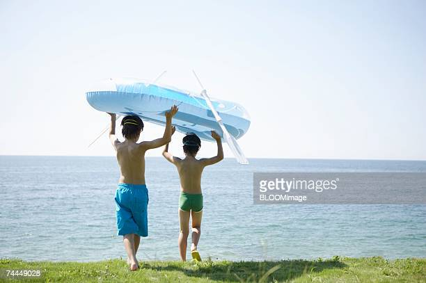Japanese boys walking with holding vinyl boat