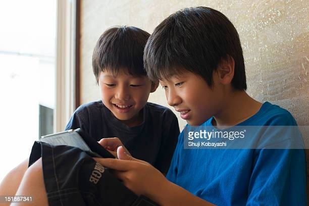 Japanese brothers playing a game on a tablet PC.