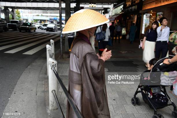 japanese buddhist monk ask for charity at downtown street of ueno, tokyo, japan - komuso stock photos and pictures