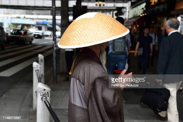japanese buddhist monk at downtown street of ueno, tokyo, japan - komuso stock photos and pictures