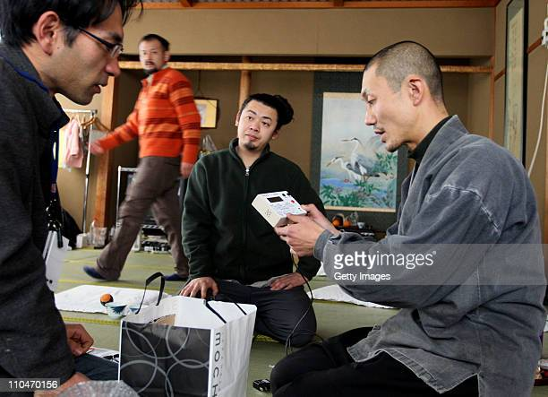 Japanese Buddhist monK Tanaka Tokuun who was evacuated from Fukushima prefecture looks over an instrument measuring radiation levels at a hotel March...