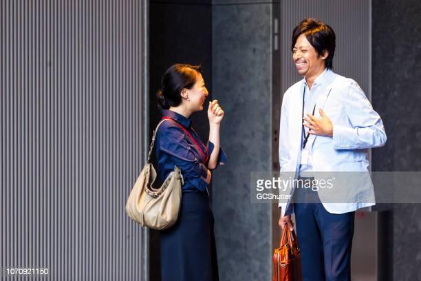 カジュアルな議論を持つ日本ビジネス部門の同僚 - 待つ ストックフォトと画像