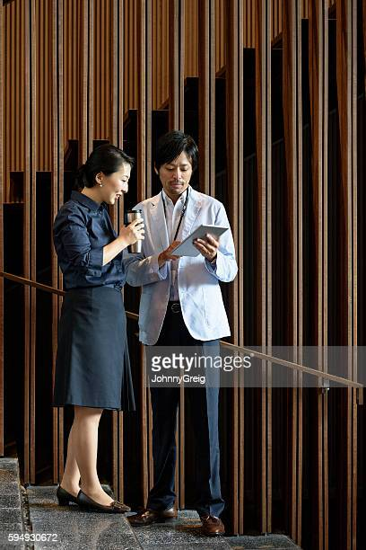 japanese business colleagues with tablet outside modern office building - ミッドアダルト ストックフォトと画像