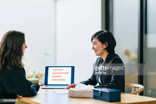 japanese business consultant giving advice to her client at home - east asia stock pictures, royalty-free photos & images