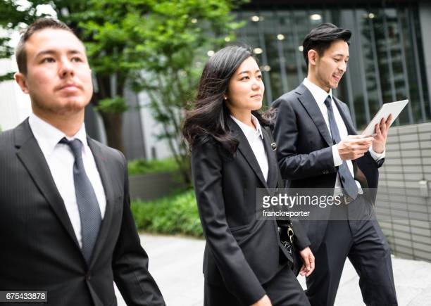 japanese business friends walking together on the street