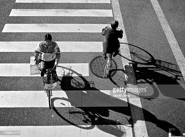 Japanese business man and woman carrying a large case pass by each other on bicycles, creating long shadows in the afternoon sun, on a crosswalk in...