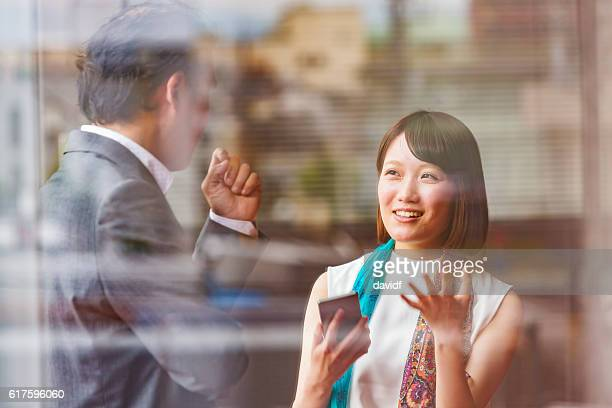 Japanese Business Man and Woman Meeting Viewed Through Office Window