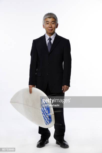 Japanese business man holding surf board.