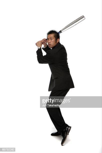 Japanese business man practicing baseball
