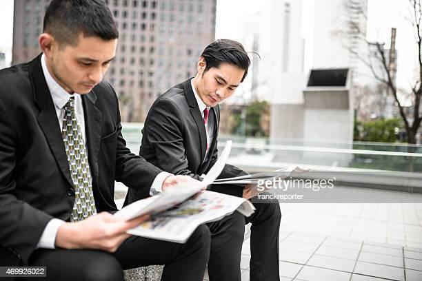 日本のビジネスの男性の読書新聞のダウンタウン
