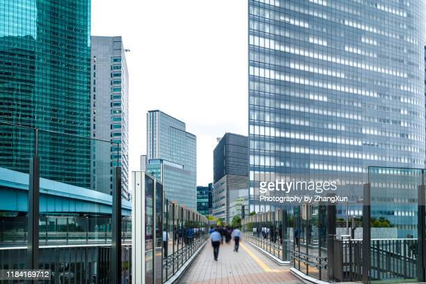 japanese business men are walking through modern office buildings in tokyo. - オフィス街 ストックフォトと画像