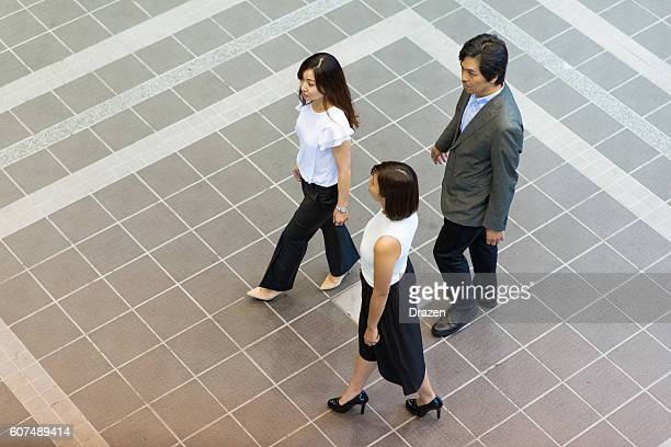 Japanese business people chat in corporate lobby