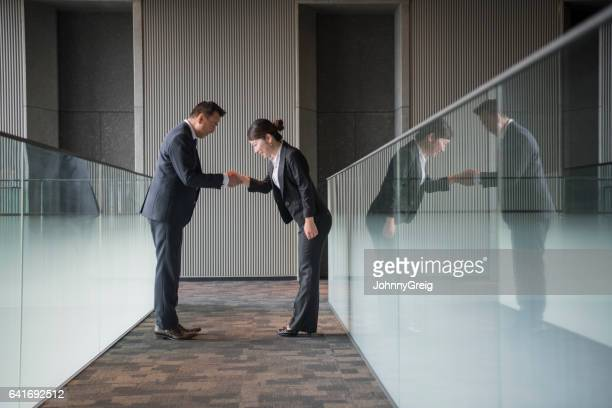 Japanese business people shaking hands and bowing