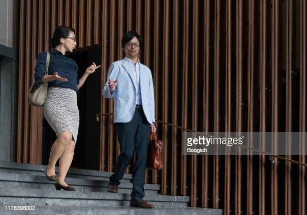 japanese business professionals walking and talking in kyoto office building - lypsekyo16 stock pictures, royalty-free photos & images