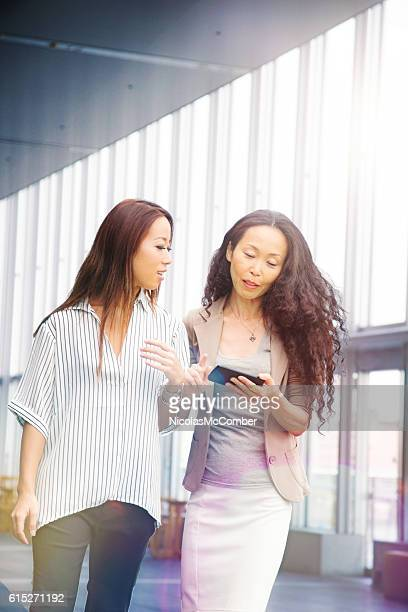 Japanese business woman share info with assistant on mobile phone