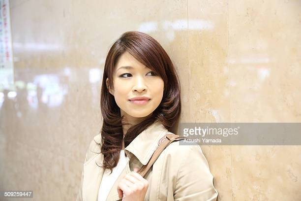 Japanese business woman standing against wall