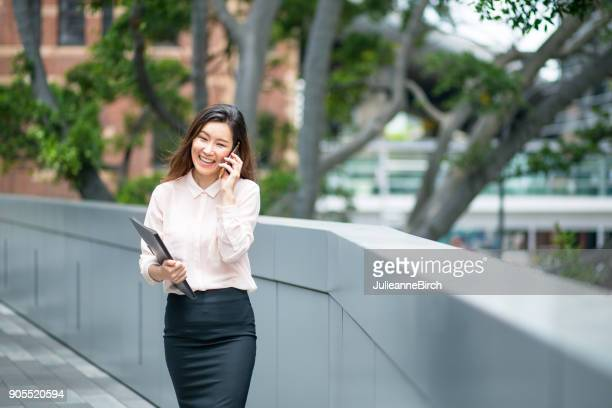 Japanese business woman walking and talking on telephone