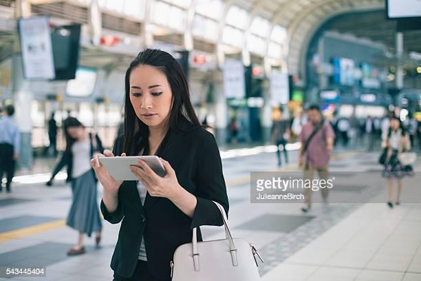 日本の女性実業家ウォーキングやに取り組んでいるデジタルタブレット - 通勤 ストックフォトと画像