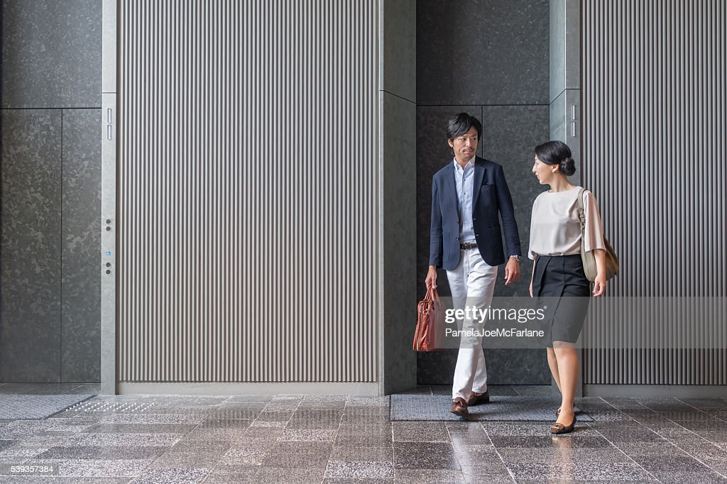 日本の実業家エレベーターを降り、仕事一色でモダンなオフィスビル : ストックフォト